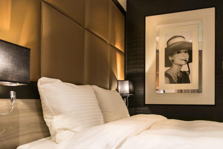 Luxe stijlvolle hotelkamer comfot bed unieke bedachterwand bekleden panelen